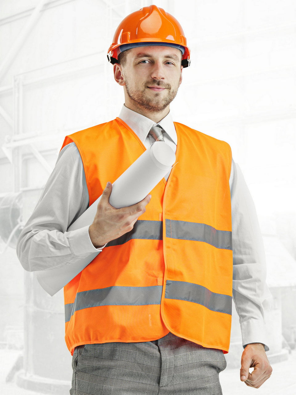 The builder in a construction vest and orange helmet standing against industrial background. Safety specialist, engineer, industry, architecture, manager, occupation, businessman, job concept