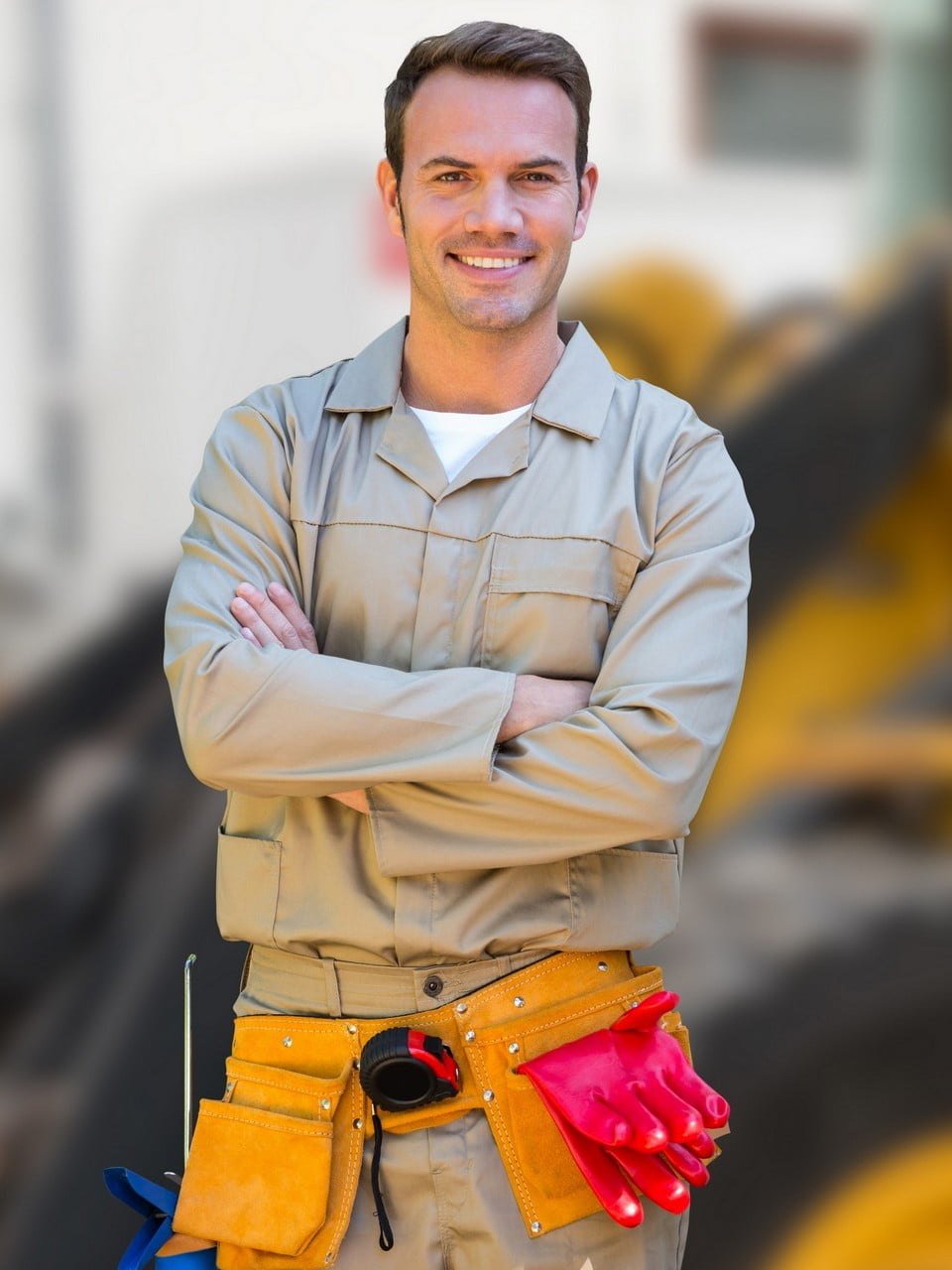 Digital composition of worker standing with arms crossed against construction site in background